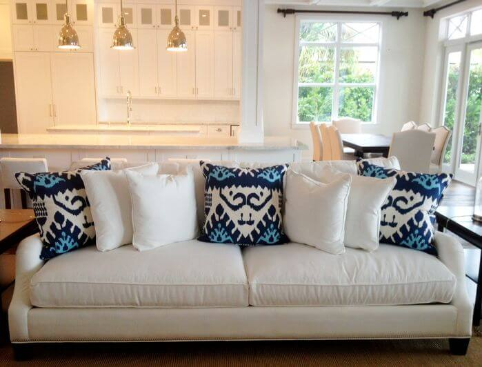 White sofa with white and blue throw pillows.