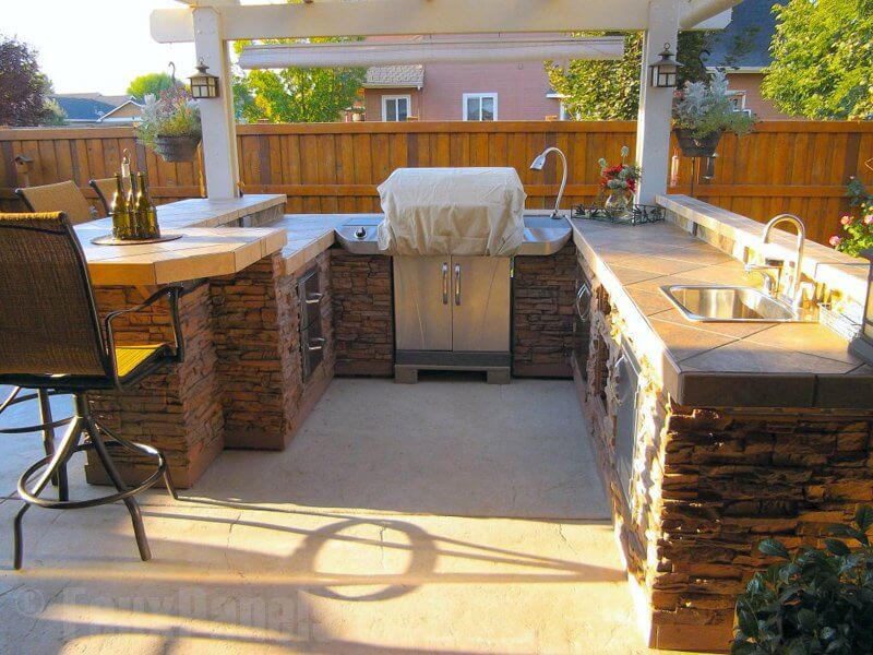 This outdoor kitchen area is wrapped in faux stacked stone, lending a decidedly elegant air to the patio entertainment area.