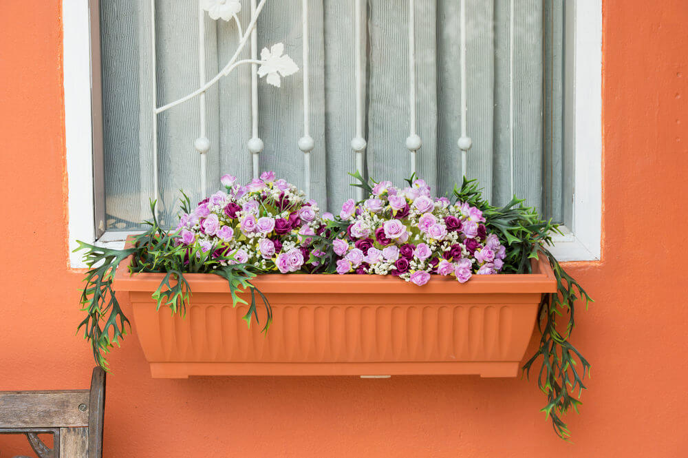 Example of a flower box painted the same colour as the wall of the home placed under a white framed window filled with light pink and purple flowers.