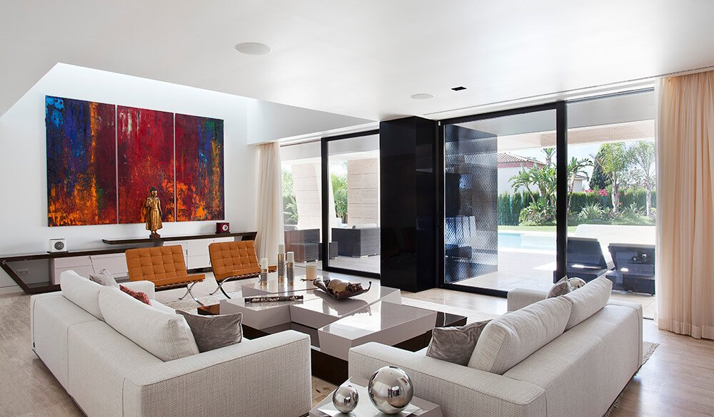 This living room looks out to the pool area through the massive windows and sliding glass doors. All of these elements, with the addition of the varied height in the ceiling, give a spacious and wide open feel. Reflective elements and minimal clutter accentuate the feel.