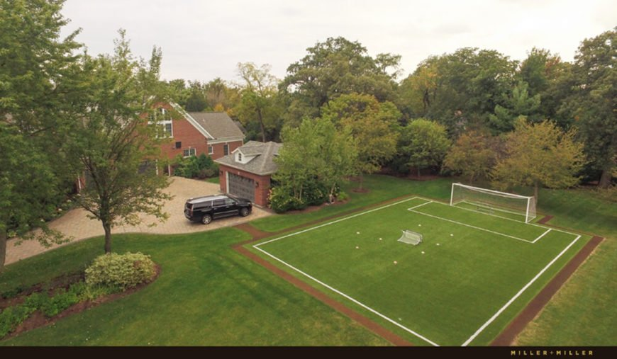 To the side of the main set of buildings, we see a half-size soccer field, one of many athletic amenitites that aren't normally found with even the largest of homes.
