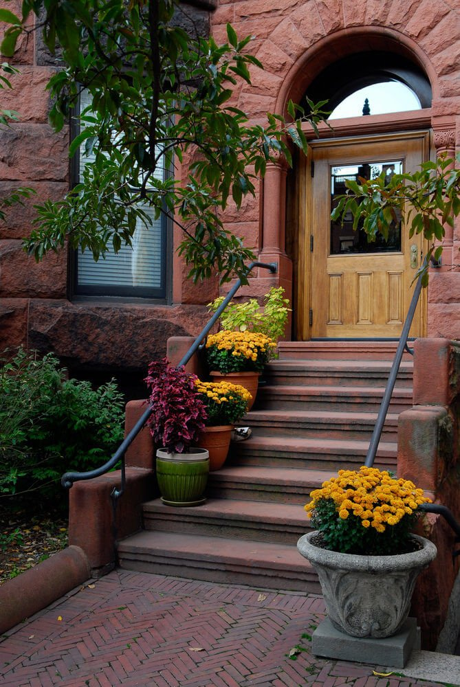 Simple and elegant stone planters and ceramic pots frame a stone staircase with luscious yellow marigolds and other deep green plants.