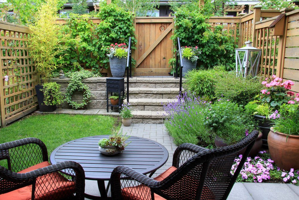 Stunning backyard patio system filled with potted plants and flowers throughout creating a small yard garden oasis.