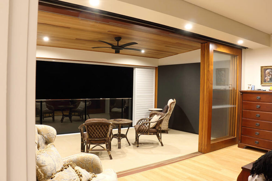 Here on the upper floor, we see the private balcony access from the bedrooms through large sliding glass and wood doors. The balcony features the same rich wood ceiling as found on lower floors.