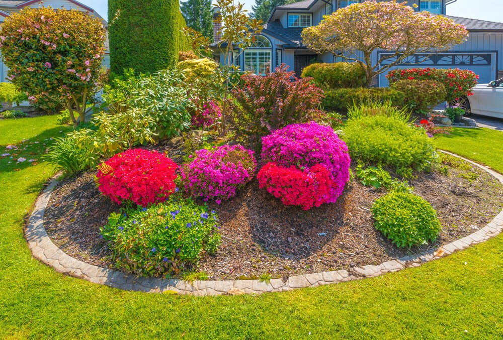 Large round garden with bright pink and red flowers with brick edge in front of 1990's style home.