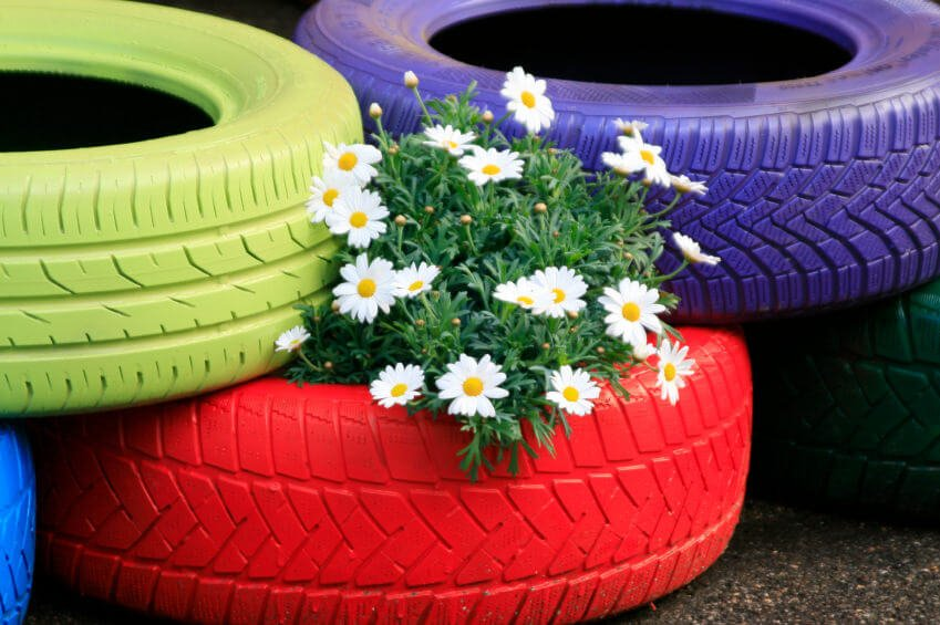 Close-up of painted tires stacked on top of one another to create a flower garden.