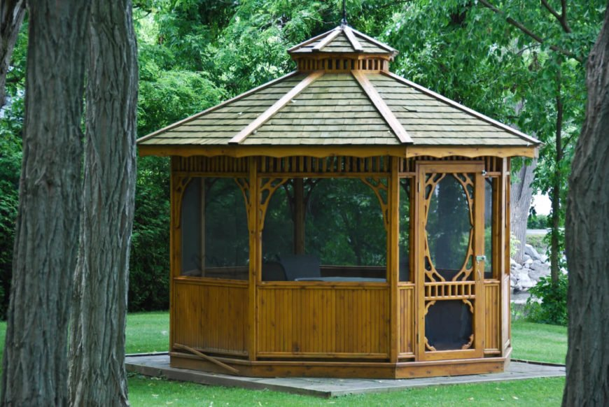 This wooden gazebo has wooden details that make it attractive and stylish. The screens are built into the walls and are lined by great wood details.
