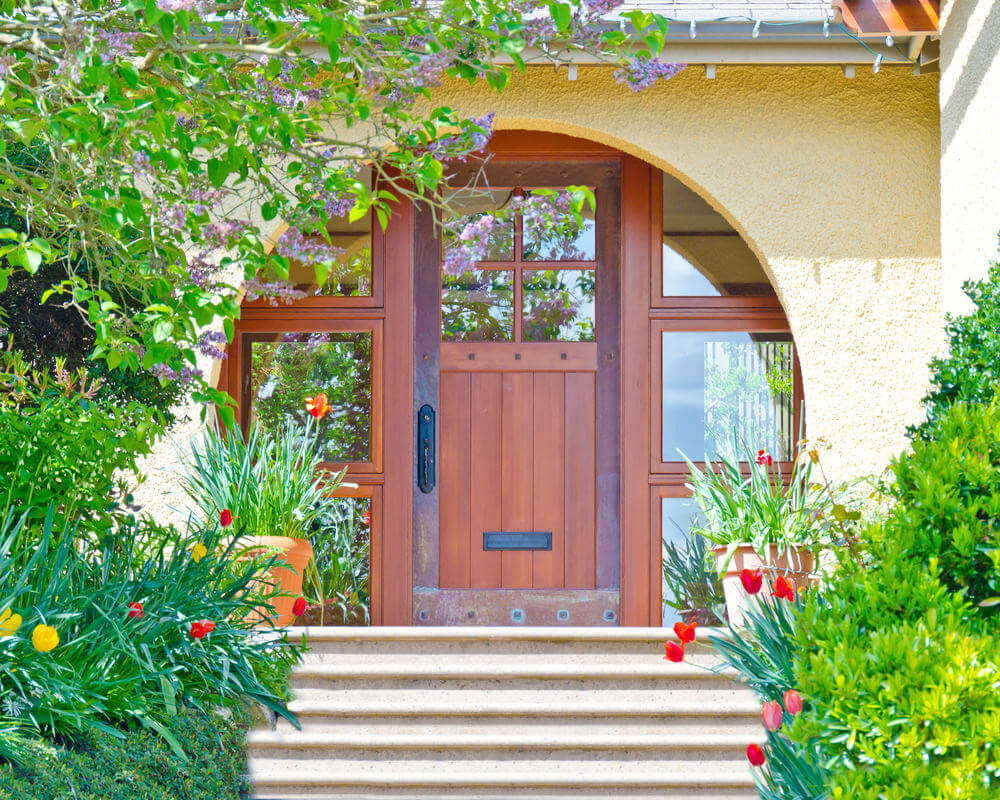 These door steps are flanked with green bushes and stunning blossoms of tulips and daffodils.