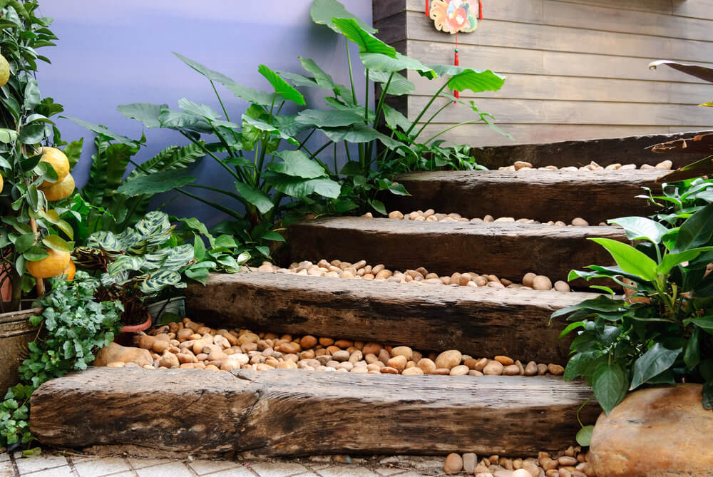 The oriental feel of these garden steps is thanks to the combination of the wood planks loaded with pebbles in between. Broad-sized green leaves and a lemon plant, complete with its fruits, serve as ornaments to this neutral-colored environment.