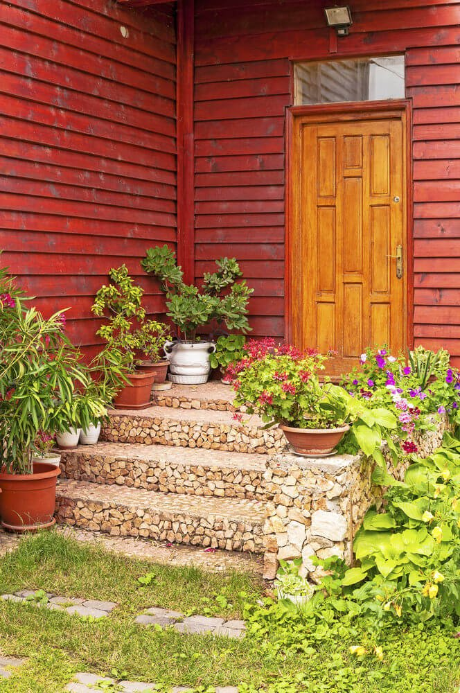 Good thing the steps have been simply done with no striking colors as it would not allow colorful plants to sit around. However, the wall and door are painted brighter with red and caramel colors, thus plants and pots should be a bit lighter so it won't contrast.
