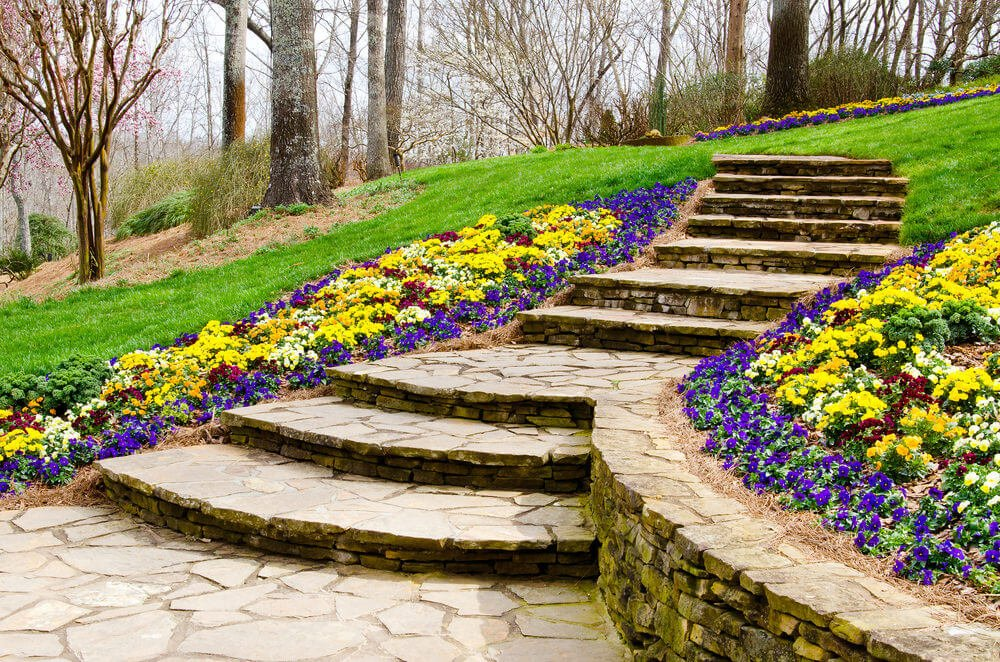 Arching stony steps are thrust in the green grassy slope leading to the woods. Deliberately planted right beside it are the colorful perennial flowers to highlight the arching stony steps through its contrast of colors.