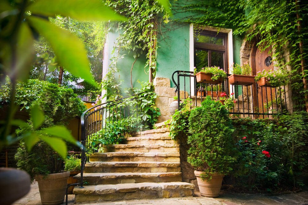 Two huge clay pots rest at the base of the staircase while hanging planters grow plants on the upper metal railings. No extra blossoming plants but a few of the flowers are visible while vines and green bushes grow abundantly around.