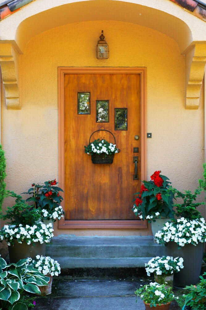 A hanging white petunia in a basket along with potted ones are highlighted with red puffy blossoms covering the front door with brilliance.