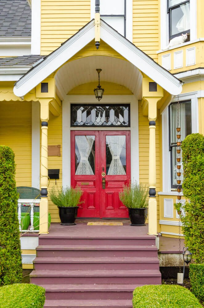 Standing on the doorsteps' sides are topiary posts while standing against the doors are black ceramic pots planted with greenery.