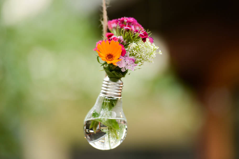 Close-up of a lightbulb used to hold a tiny colourful flower bouquet.