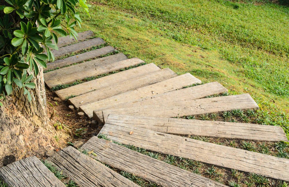 These garden steps are made up of wood planks, making a curve around the bend downwards on the green grassy slope.