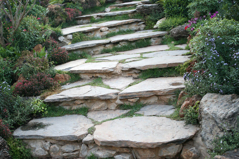 Flowery shrubs seem to usher in guests toward these huge pieces of stone slabs that serve as garden steps where grasses have found their way through the cracks within.