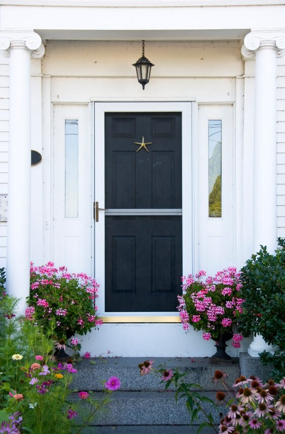 Potted honeysuckle along with blossoming daisies, chamomile and marigolds accent this front door.