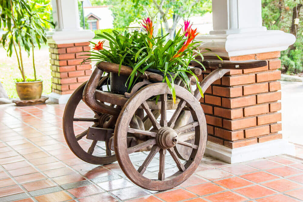 Here's pot creativity with this wooden wagon flower planter on a veranda.