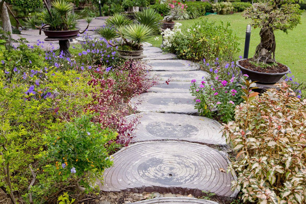 Slices of wood slabs attract a lot of attention as this garden's pathway is surrounded by flowering plants and low-lying shrubs.