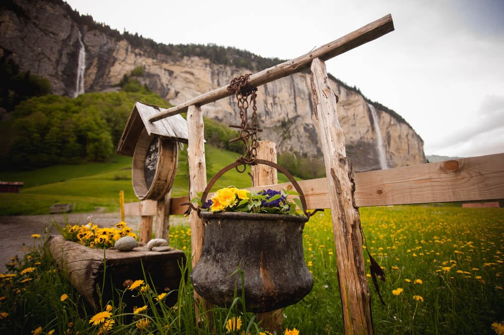 An old well bucket hanging from the log style beam turned into a large hanging basket.