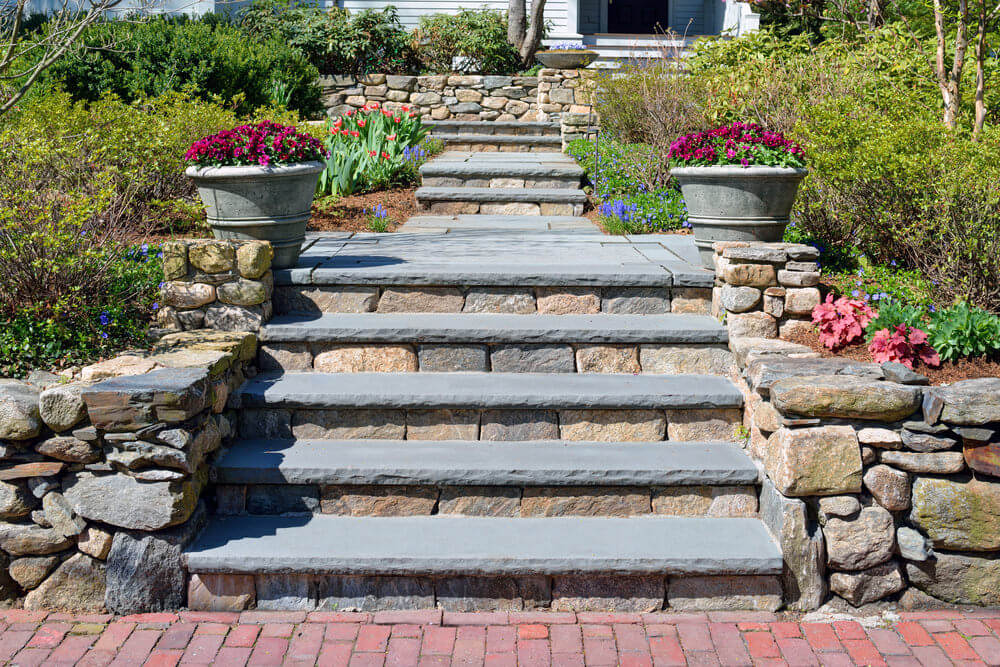Having outdoor steps in the middle of so many green plants could be difficult to decorate. A display of two huge grey pots planted with red flowers is a good idea for simplicity and elegance.
