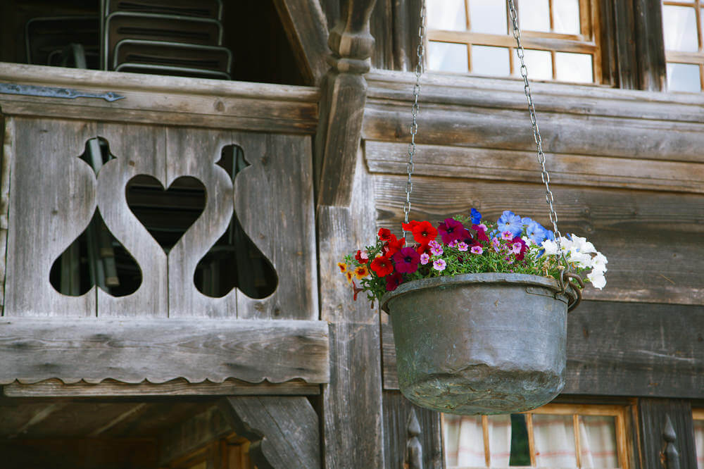 Metal bucket use to hold a variety of flowers and a colourful arrangement suspended by matching silver chain from a wooden beam.