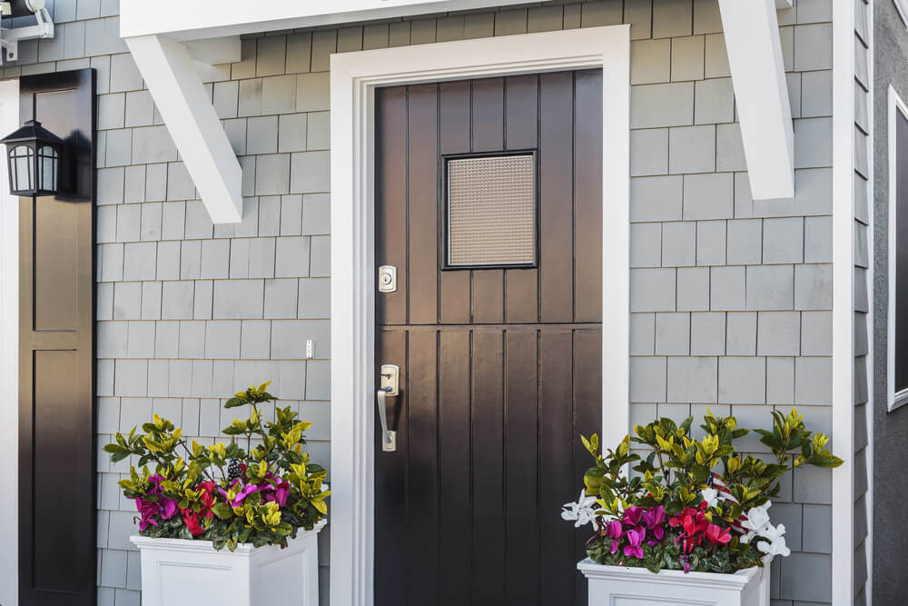 These plants ornament the plain and simple looking front door with their colorful blossoms.