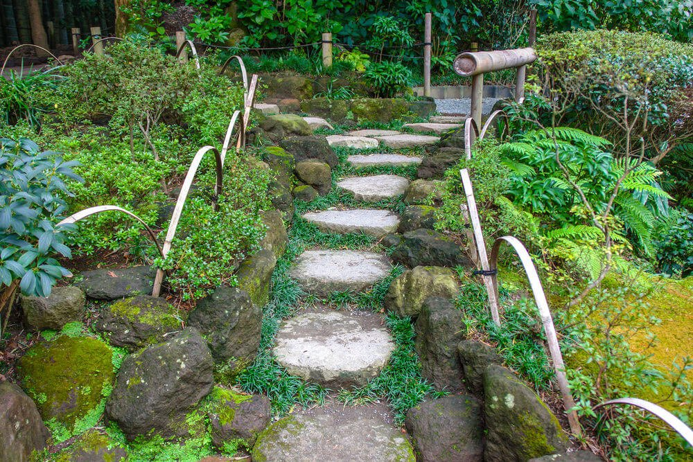 Dark mossy boulders together with bamboo slats and bamboo shoots serve as dividers, separating the ferns and shrubs from garden steps made up of slabs of stone.