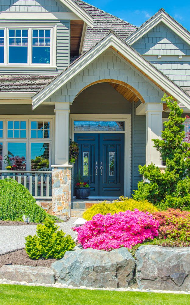 The fancy house decoration is paired with bushes of colorful petunias and green shrubs. Along with these are huge rocks assembled to provide elevation to the landscape.