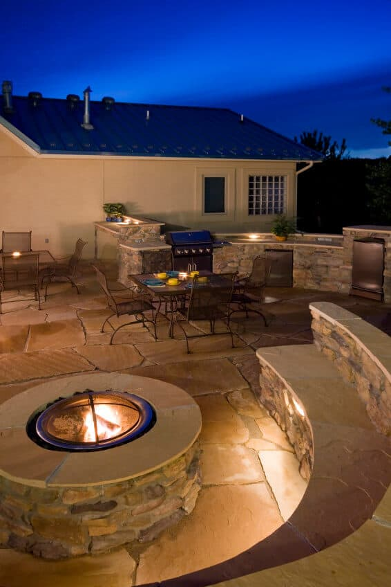 Round brick fire pit with flat top and dome cover on large flagstone patio with built-in semi circle seeding wrapping around the fire pit.