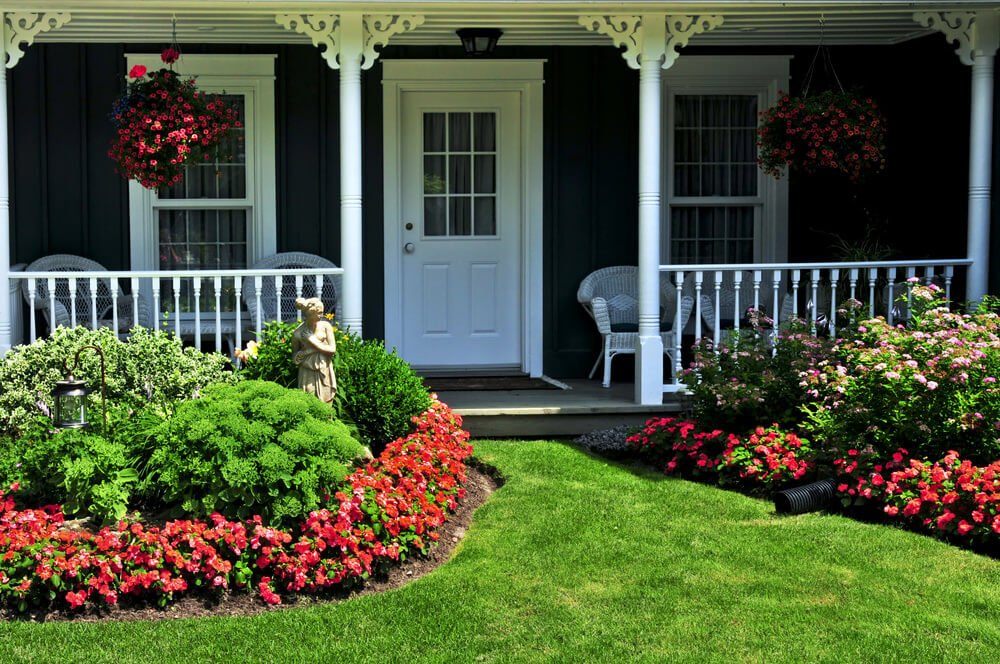 The garden of healthy grasses and shrubs house a welcoming woman figure resting behind the bush and colorful blooms of petunias. It is also decorated with a lampshade that lights the grassy path at night.