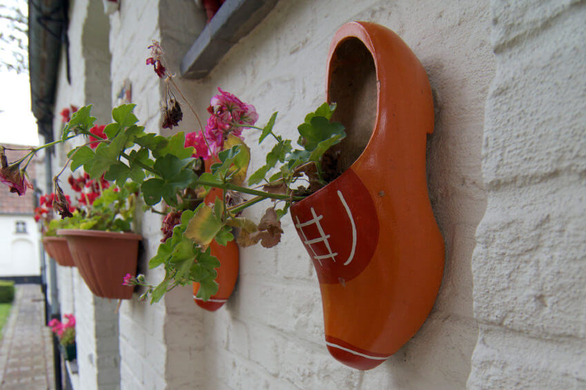 Whitewashed walls are good backdrops for wall mounted clay flower pots. You can also add in orange clogs for some splash of playfulness and fun feel. Flower plants look great in the clogs, too.