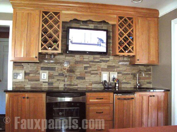 The use of several distinct colors in the faux stone backsplash ensures contrast while also picking up subtle tones out of the warm, light wood cabinetry and wine racks.
