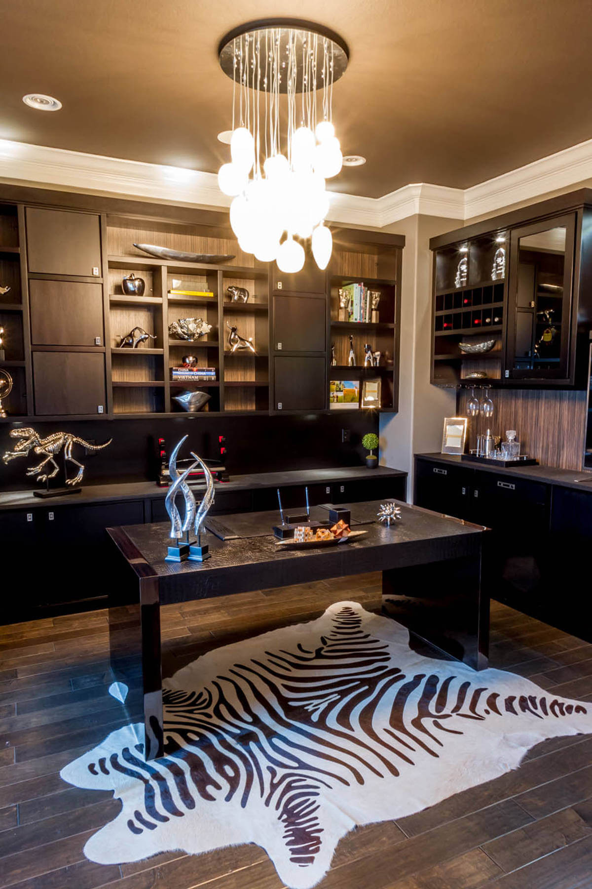 I love home offices with extensive custom cabinets for storage, display and workspace. This home office has that in spades. It's an insanely nice place to work with the dark cabinetry and desk and zebra print area rug