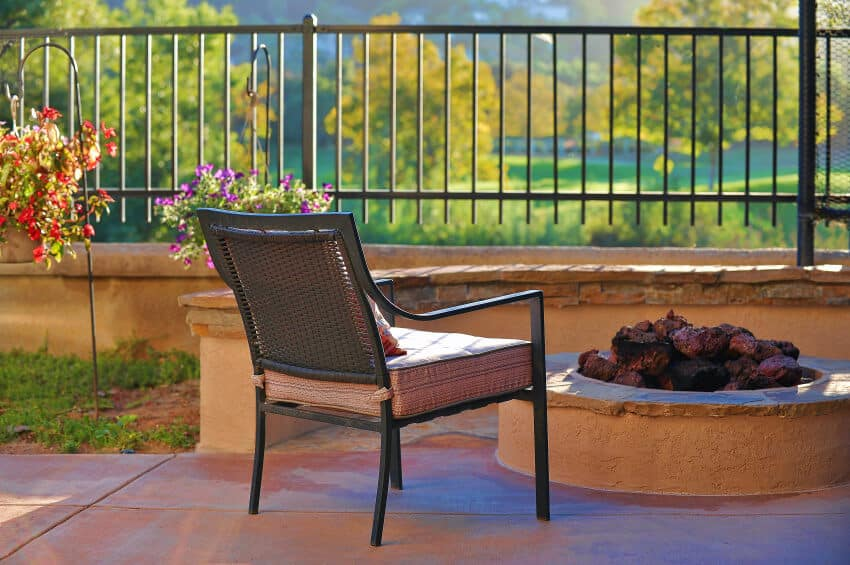 Small round stucco covered built-in fire pit on patio.