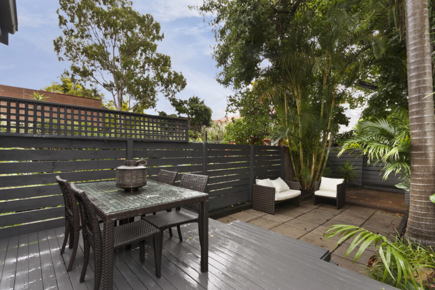 Floating decks are often designed and colored to match their environment. This design features grey paint to match the surrounding privacy fence, providing an elevated dining space in the yard.