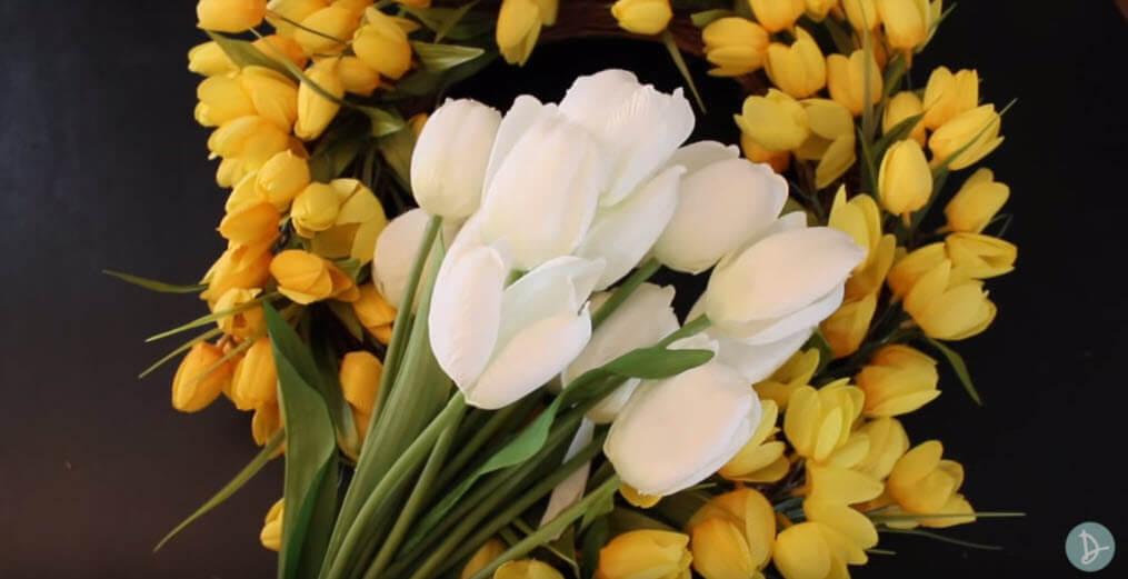 Adding white flowers to yellow Spring wreath
