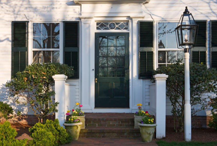 Pine shrubs, small trees, and potted daisies flank the edges of this front entry.