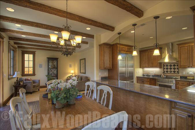 This lovely kitchen looks out over the dining room, which features horizontal faux beams all the way across, extending down to the adjacent living room.