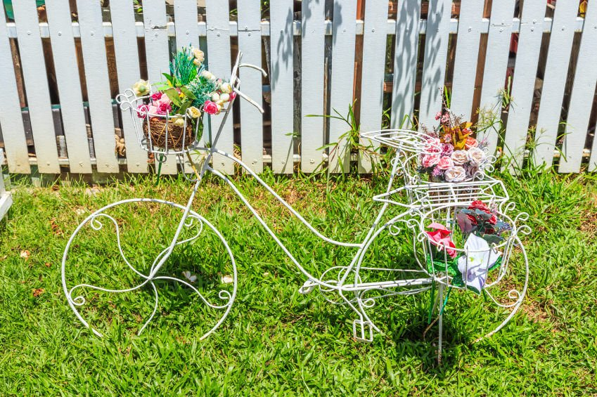 Whimsical white bicycle sculpture with flower pot holders.