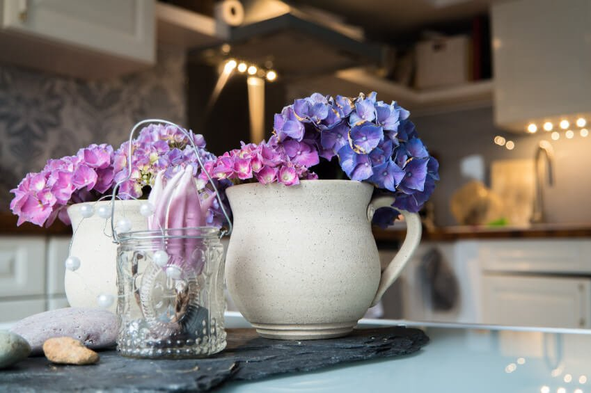 Use water-pitchers as vases with your hydrangeas to give a country and rustic vibe to your table top. This would help you give color to your kitchen or dining room.