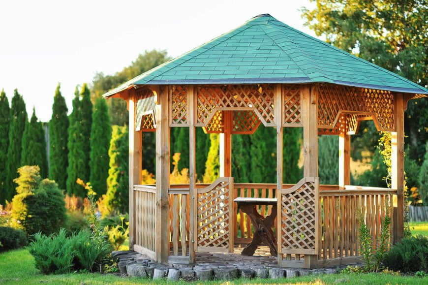 This cute gazebo has a lattice, wooden features, and fence. The stone floor gives this structure a strong base that is perfect for a sturdy backyard gazebo that will last for years.