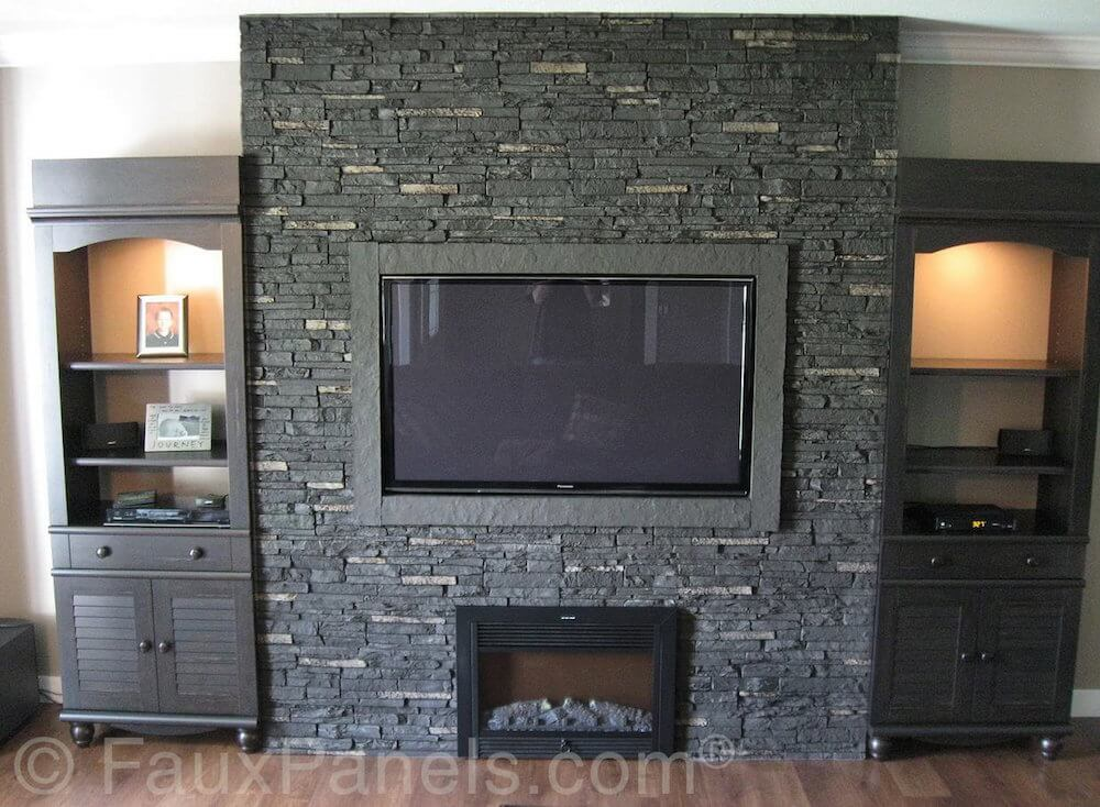This is a gorgeous example of a dark stone facade on a fireplace surrounded fitted with a large television and cabinetry on either side.