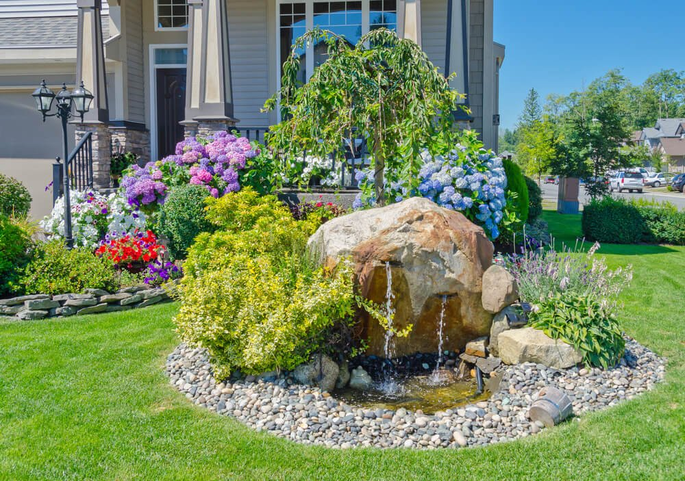 A cool water fountain from a large rock gives a refreshing view. Around its edges are stones and grasses while blossoming mopheads and petunias gives life at the back.