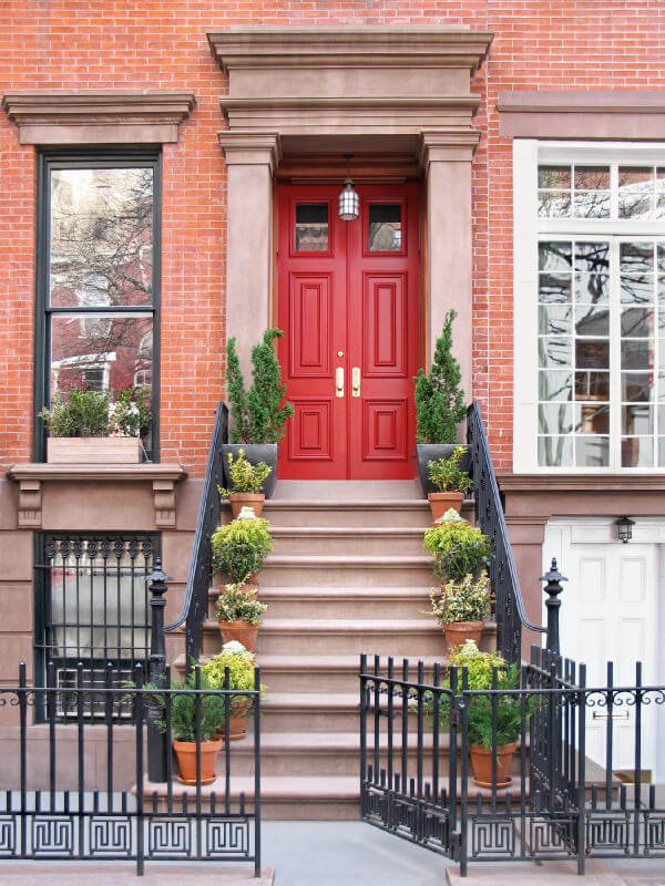 Non-flowering plants can be decorative and complementary with the red front door. It provides a calming color combination and does not appear over designed with its natural colored pots. Moreover, the larger grey pots conclude the parallel rows of potted greenery.
