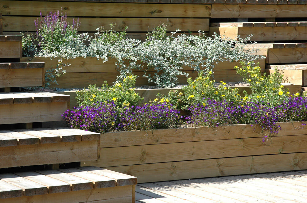 This tiered patio wood planter is a fabulous way to border a deck in small backyard.