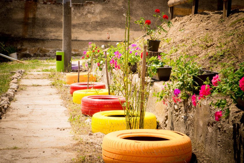 Painted tires lined up against a retaining wall in a line ready to serve as planters.