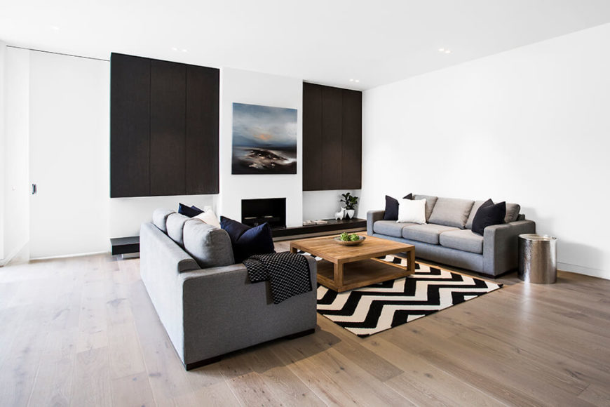 The living room is defined by a pair of matching grey contemporary sofas, centered on a large rustic wood coffee table and zebra stripe rug. The rich hardwood flooring, in a lighter shade, meshes with the white walls.