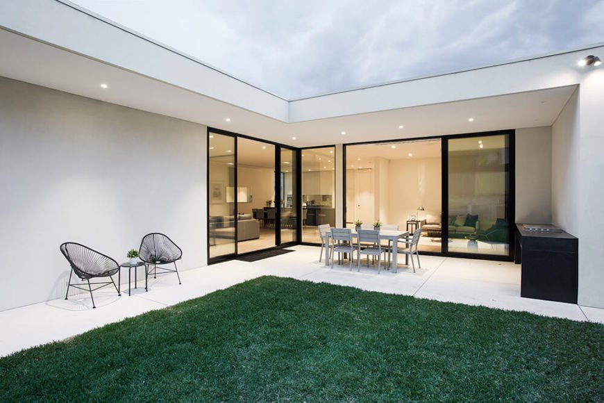 Here's a look at the home from the backyard, where the plush lawn meets a light concrete patio, leading directly into the interior. A set of dining furniture and cooking counter out here make for a comfortable patio space.
